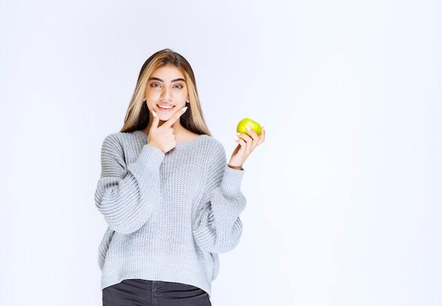 Mädchen im grauen sweatshirt, das grünen apfel in der hand hält.