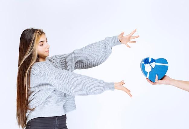 Mädchen im grauen sweatshirt, das hand sehnt, um eine blaue herzform-geschenkbox zu nehmen.