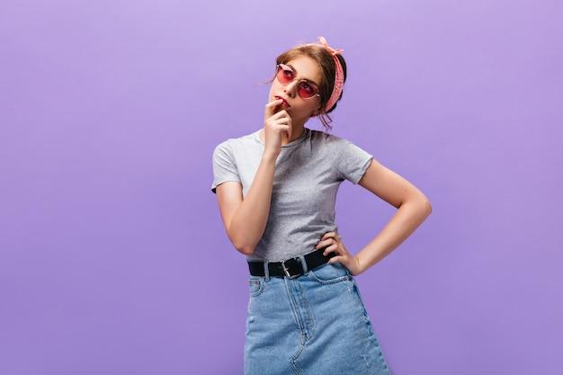 Mädchen im grauen t-shirt und im jeansrock wirft auf lokalisiertem hintergrund auf. schöne junge frau in der stilvollen rosa sonnenbrille und im coolen outfit, das oben schaut.