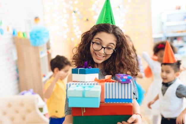 Mädchen im grünen festlichen hut freut sich an der großen anzahl der geschenke.