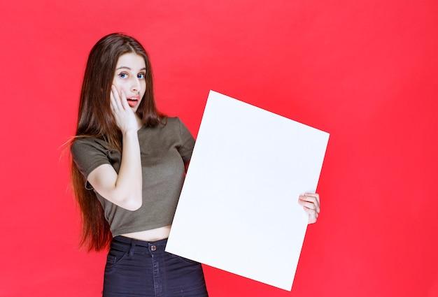 Mädchen im grünen hemd, das einen großen leeren quadratischen infoschreibtisch hält und schaut verwirrt und überrascht aus.