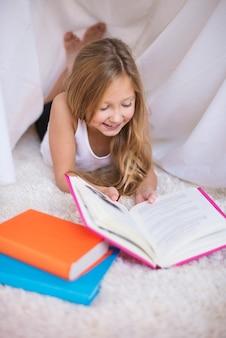 Mädchen im grundschulalter liest ein buch
