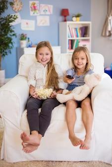Mädchen im grundschulalter warten auf ihr lieblingsfernsehprogramm