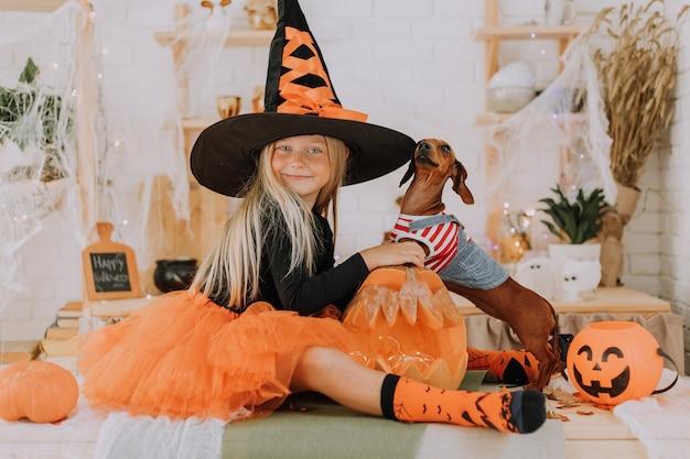 Mädchen im halloween-hexenkostüm und ein winziger dackel im hundeoverall sitzen auf dem boden