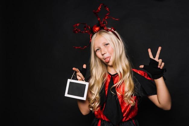 Mädchen im halloween-kostüm gestikulierend und gesicht verziehend
