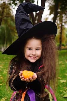Mädchen im halloween-kostüm und im hut der hexe mit kleinem kürbis in den händen
