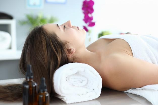 Mädchen im handtuch liegt an der rezeption massagetherapeutin