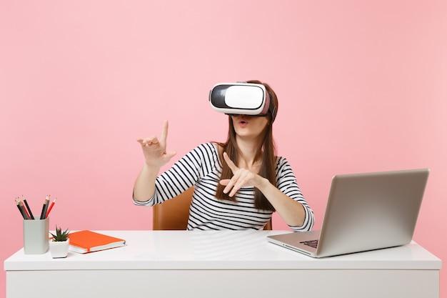 Mädchen im headset der virtuellen realität auf dem kopf berühren so etwas wie knopfdruck oder zeigen auf schwebende virtuelle bildschirmarbeit am schreibtisch mit laptop einzeln auf rosafarbenem hintergrund. erfolg geschäftskarriere.