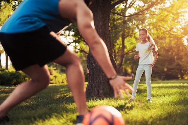 Mädchen im hellen angefochtenen anzug spielt fußball mit ihrem vater.