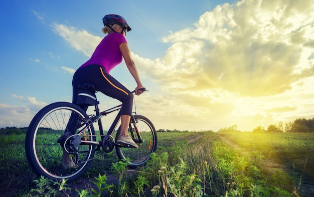 Mädchen im helm auf fahrrad schaut in die ferne