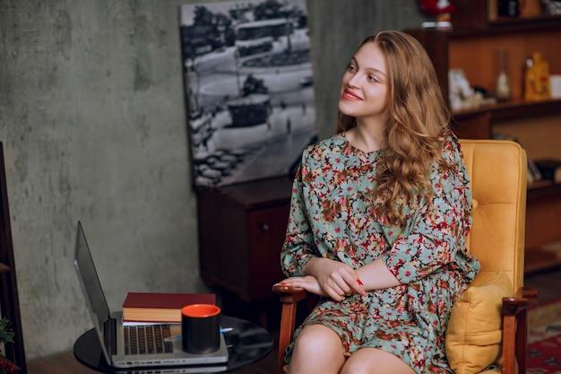 Mädchen im herbstwinterblumenkleid, das sitzt und lächelt.