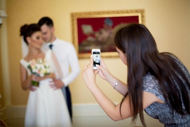 Mädchen im hotel macht fotos von bräuten am telefon