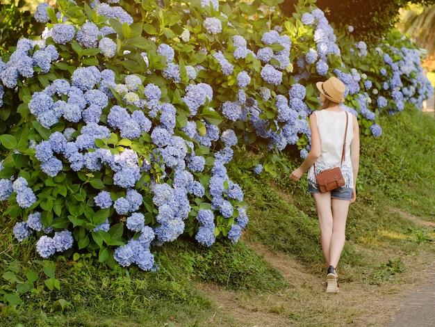 Mädchen im hut geht im park entlang der blühenden büsche