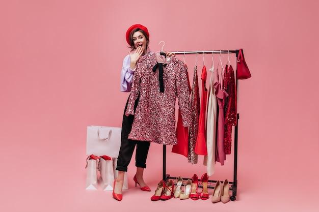 Mädchen im hut in freudiger überraschung hält kleiderbügel mit glänzendem kleid. porträt der frau zum zeitpunkt des einkaufens auf rosa hintergrund.