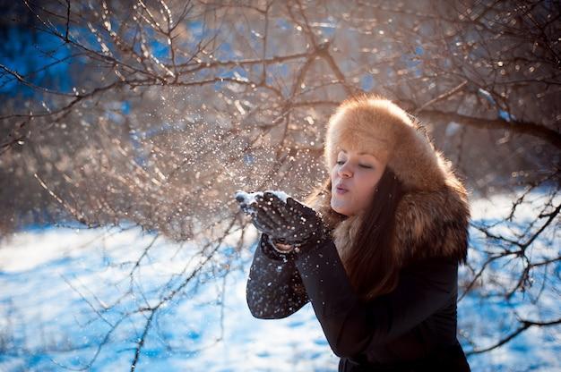 Mädchen im hut mit den ohrenklappen, die auf dem schnee durchbrennen.