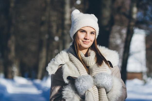 Mädchen im hut und in den handschuhen lächelnd im winter