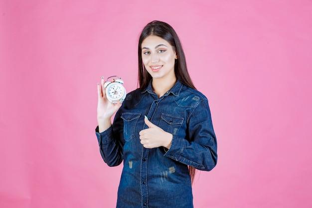 Mädchen im jeanshemd, das den wecker hält und gutes zeichen macht