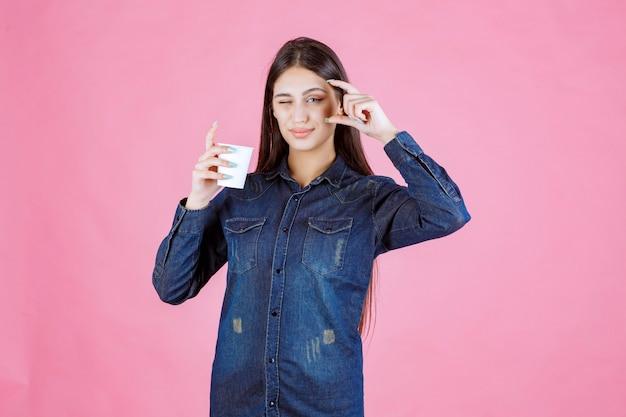 Mädchen im jeanshemd, das die menge des kaffees in der tasse zeigt