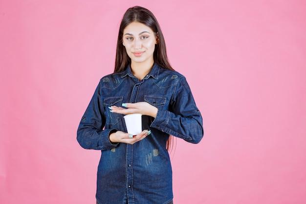 Mädchen im jeanshemd, das eine kaffeetasse zwischen ihren händen hält