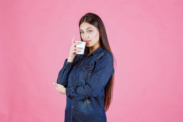 Mädchen im jeanshemd, das eine tasse kaffee trinkt