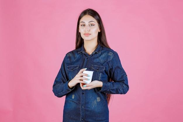 Mädchen im jeanshemd, das eine wegwerfbare tasse kaffee genießt