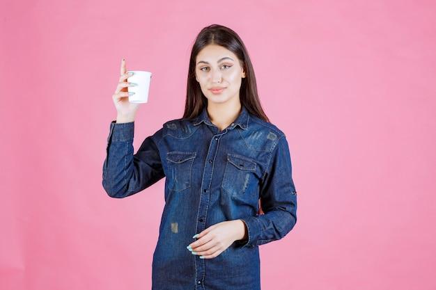Mädchen im jeanshemd hält eine kaffeetasse und fühlt sich positiv