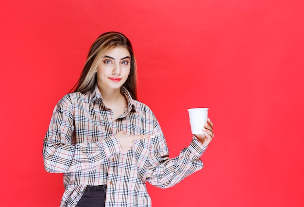 Mädchen im karierten hemd mit einer weißen einweg-kaffeetasse