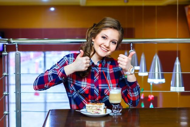Mädchen im karierten hemd zeigt gerne eine tasse mokachino und kuchen