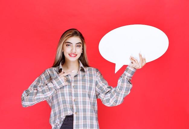 Mädchen im karierten pullover, der ein ovales ideenboard hält und mit dem finger darauf zeigt