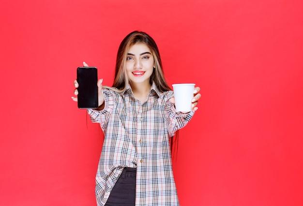 Mädchen im karierten pullover hält eine tasse getränk und zeigt ihr smartphone