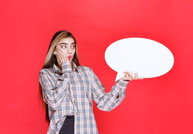 Mädchen im karierten pullover mit einem ovalen ideaboard sieht verwirrt und aufgeregt aus