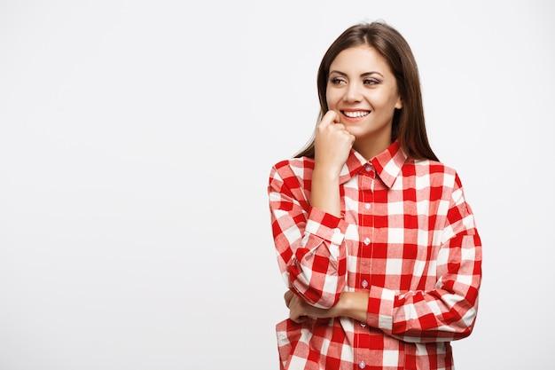 Mädchen im karohemd, das mit rechter hand auf wange aufwirft