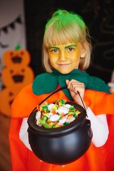 Mädchen im kürbiskostüm hält eine schüssel voller süßigkeiten