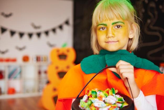 Mädchen im kürbiskostüm mit einer schüssel bonbons