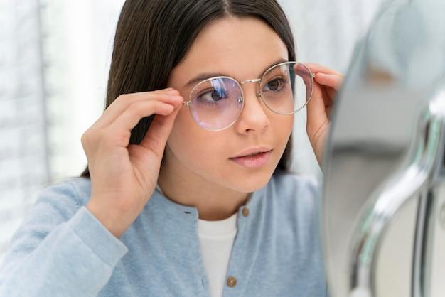 Mädchen im laden, das brille anprobiert