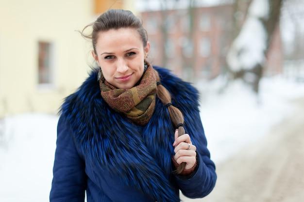 Mädchen im mantel an der winterlichen straße