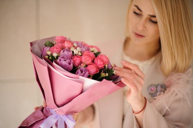 Mädchen im mantel, der den blumenstrauß von purpurroten violetten und rosa blumen betrachtet