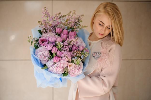 Mädchen im mantel, der einen blumenstrauß von purpurroten violetten tulpen und von flieder hält