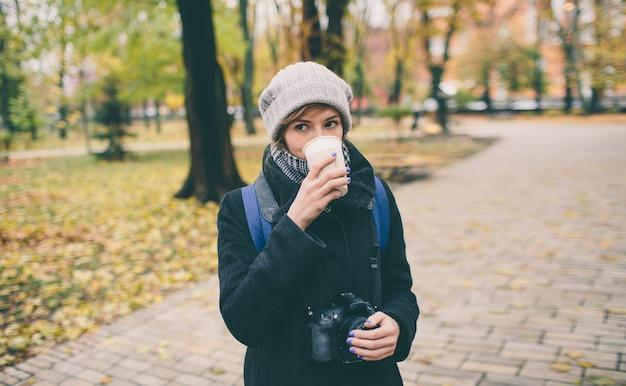 Mädchen im mantel hält eine tasse kaffee latte mit milch. einsame frau steht auf einer verschneiten herbstlichen straße im herbst im park.