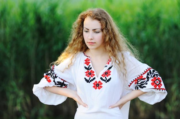 Mädchen im nationalen ukrainischen hemd auf grashintergrund