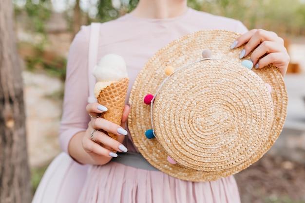 Mädchen im niedlichen lila kleid, das im freien steht und dekorierten strohsommerhut in der hand hält
