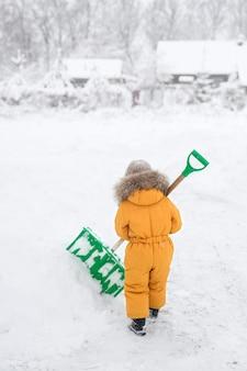 Mädchen im orangefarbenen overall reinigt große schneeschaufel