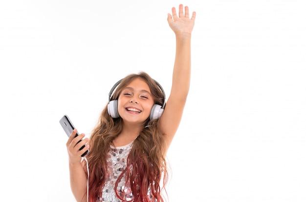 Mädchen im prickelnden kleid, mit großen weißen kopfhörern und schwarzem handy in ihrer hand ist wirklich glücklich, jemanden zu sehen, der lokalisiert wird