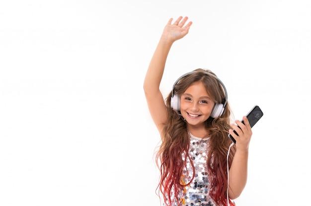 Mädchen im prickelnden kleid, mit großen weißen kopfhörern und schwarzem handy in ihrer hand