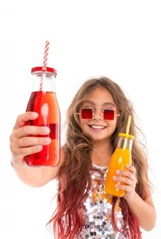 Mädchen im prickelnden kleid und in der stilvollen quadratischen roten sonnenbrille, die zwei glasflaschen mit rotem getränk auf vordergrund und mit dem gelben getränk lokalisiert hält