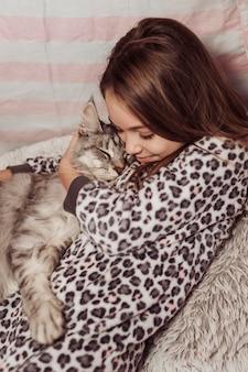 Mädchen im pyjama, das ihre flauschige katze umarmt