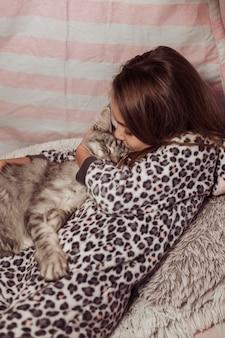 Mädchen im pyjama küsst ihre katze