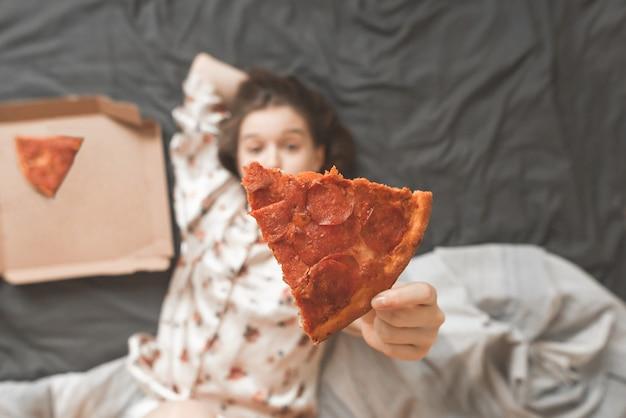 Mädchen im pyjama liegt zu hause in einem bett mit einer pizzaschachtel