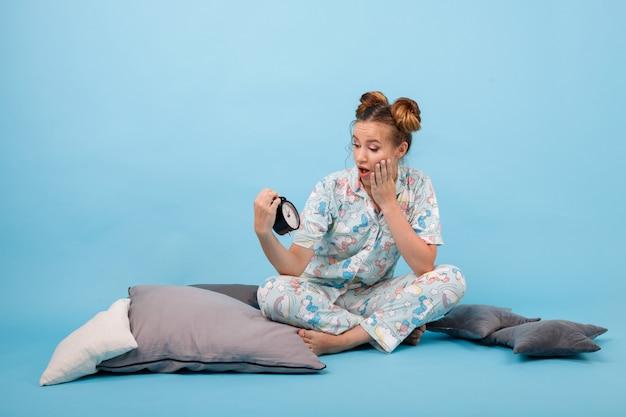Mädchen im pyjama und mit einem wecker auf einem blauen raum. guten morgen