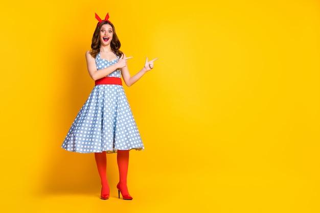 Mädchen im retro pin up dress point finger kopie raum auf gelbem hintergrund